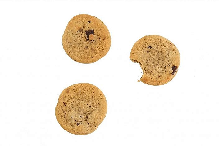 Three chocolate chip cookies one a white background.