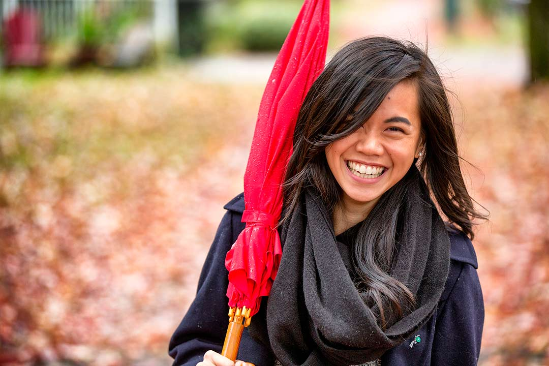 young asian woman smiles at camera holding a red umbrella over her shoulder with fall leaves in background