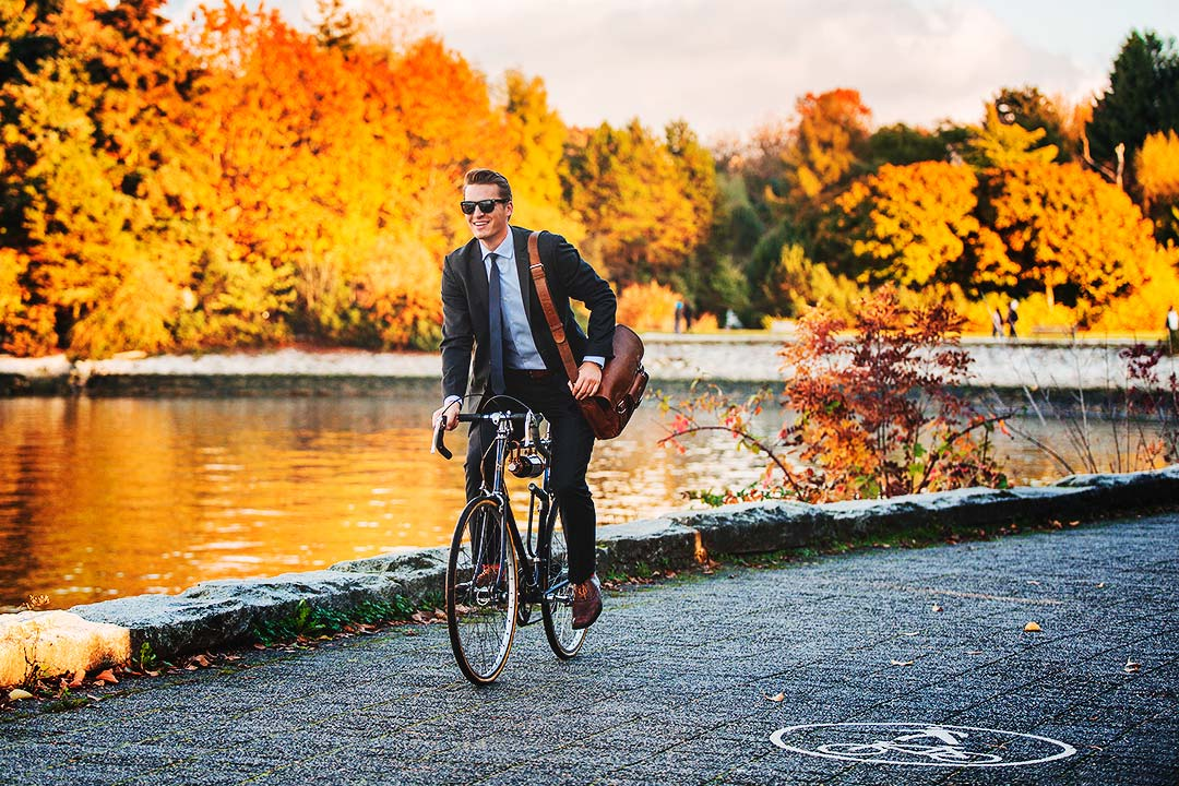 attractive man rides bicycle along the seawall with fall colours in the background