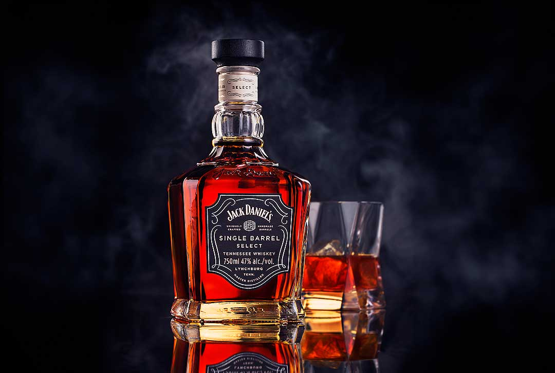 product photography branding jack daniels bottle and glass with smokey background