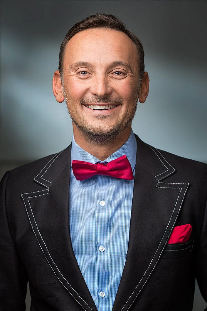 portrait photography man in suit and red bow-tie smiles