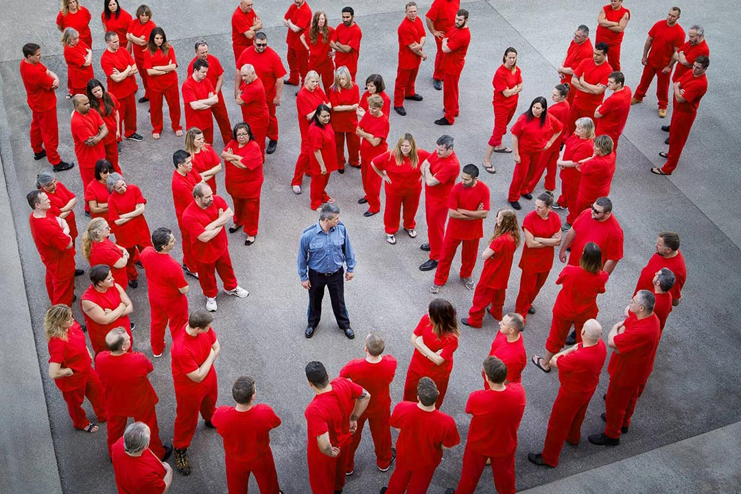 lone prison guard stands surrounded by 70 inmates wearing red