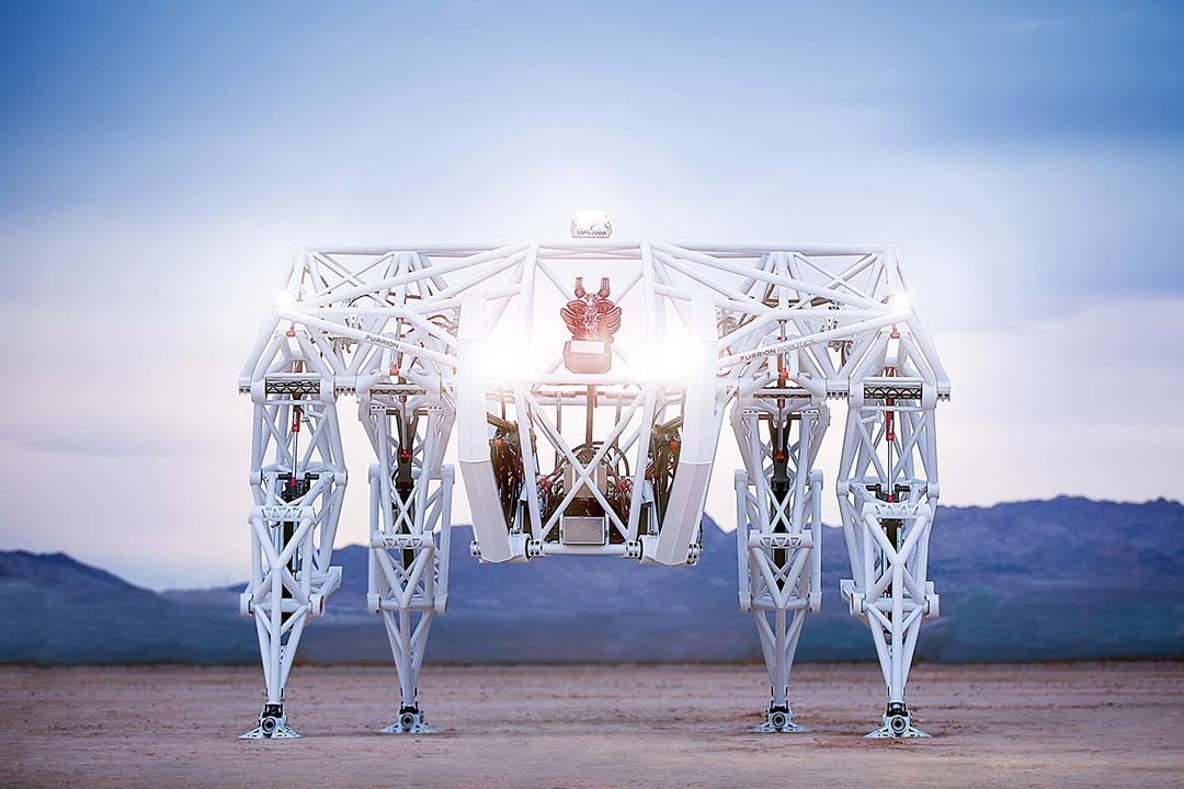 a giant white robot sits in the open desert at dawn