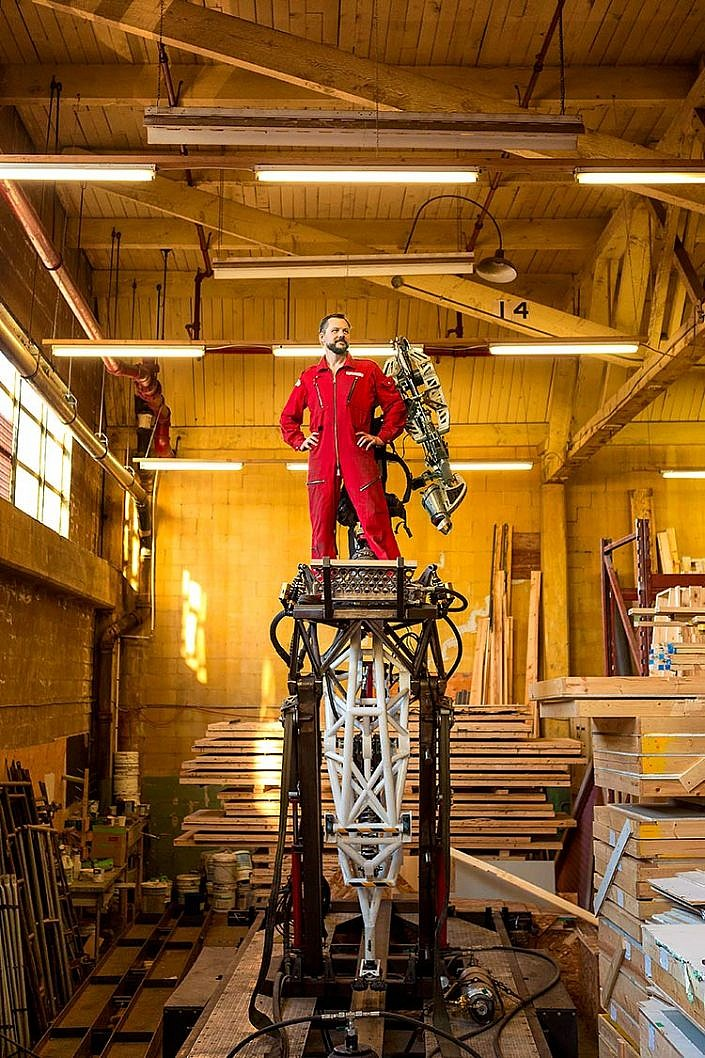 Robotics engineer Jonathan Tippett stands on a huge robot leg wearing a red jumpsuit