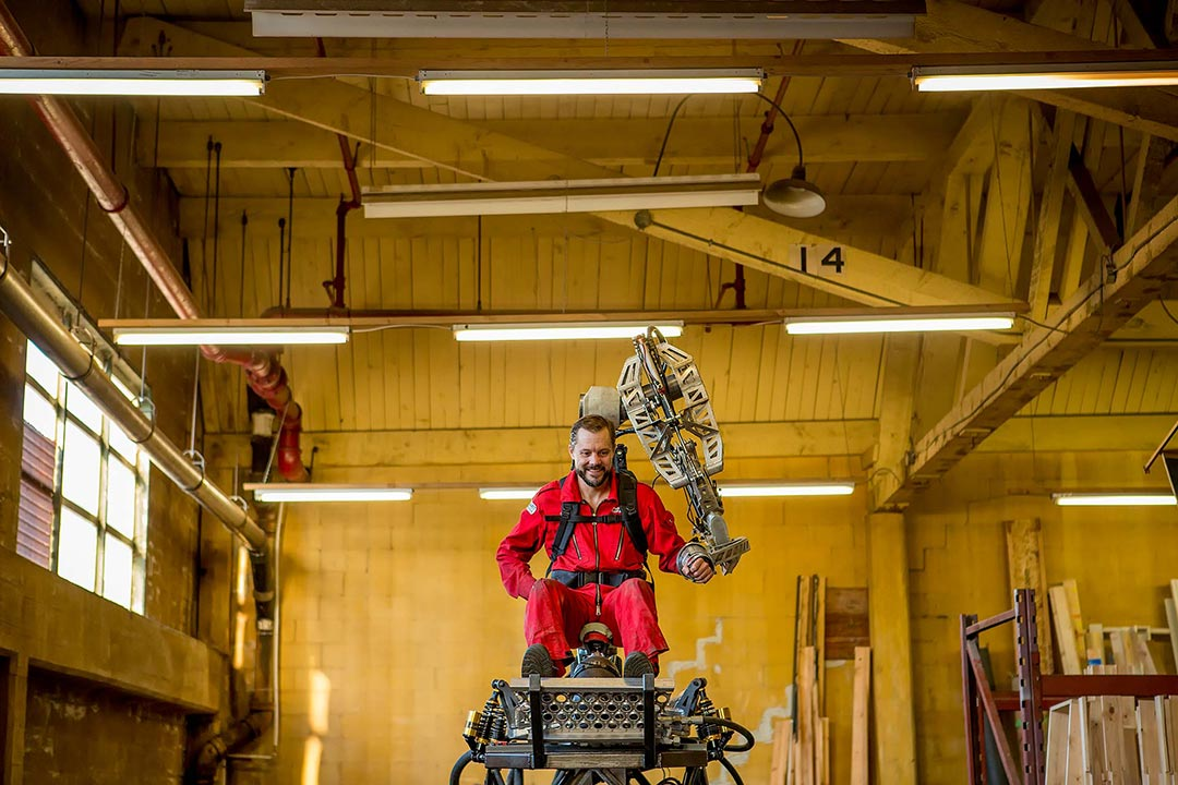 portrait photography robotics engineer jonathan tippett wears a red jumpsuit and works a mechanical arm