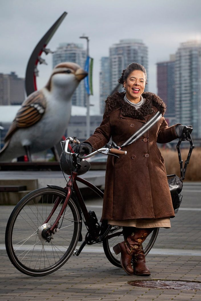 Portrait photography image of woman posing with bicycle at olympic village in Vancouver BC