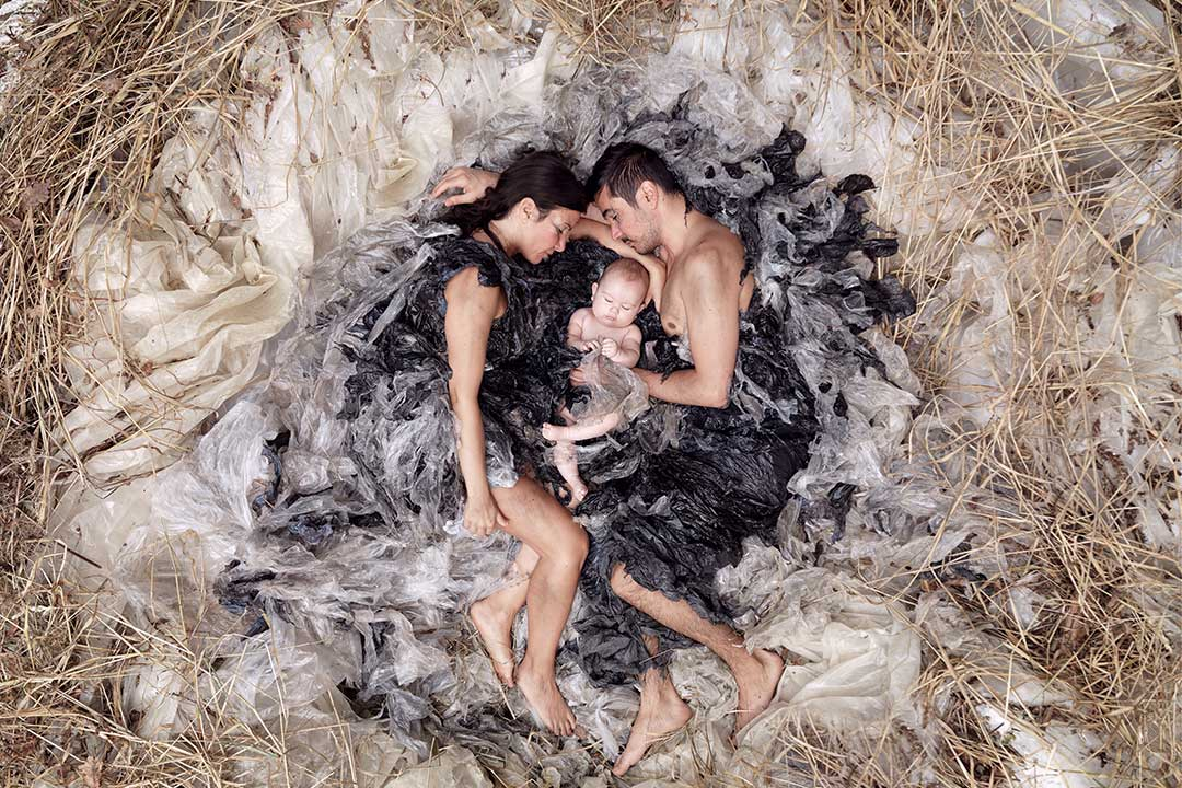 A young woman a young man and a baby are nestled in a nest of plastic waste. Michael Hall photographer