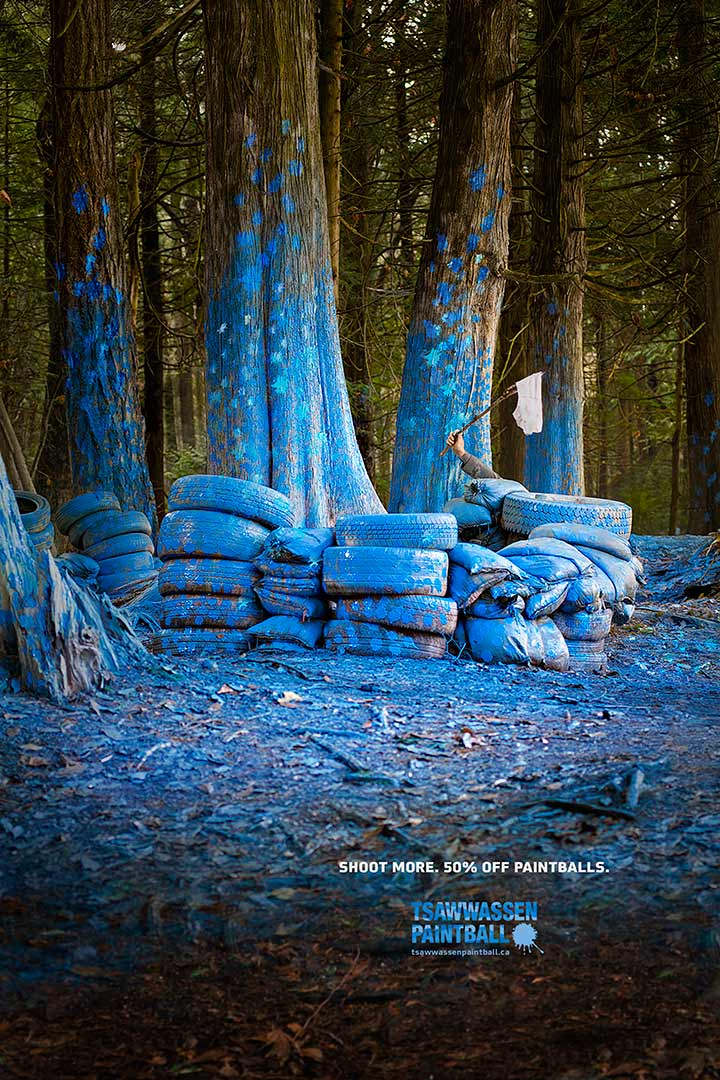paintball advertisement a forest is painted blue while a hand waves white underwear to surrender